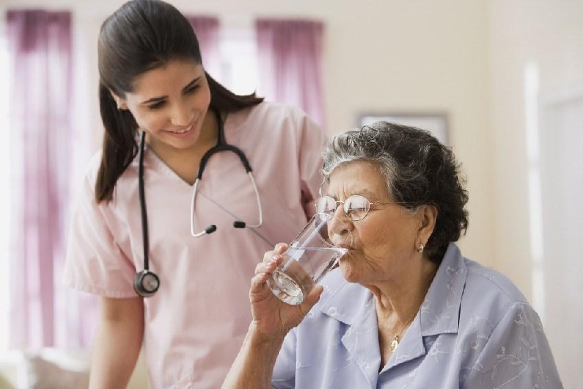 Senior Hispanic woman drinking glass of water