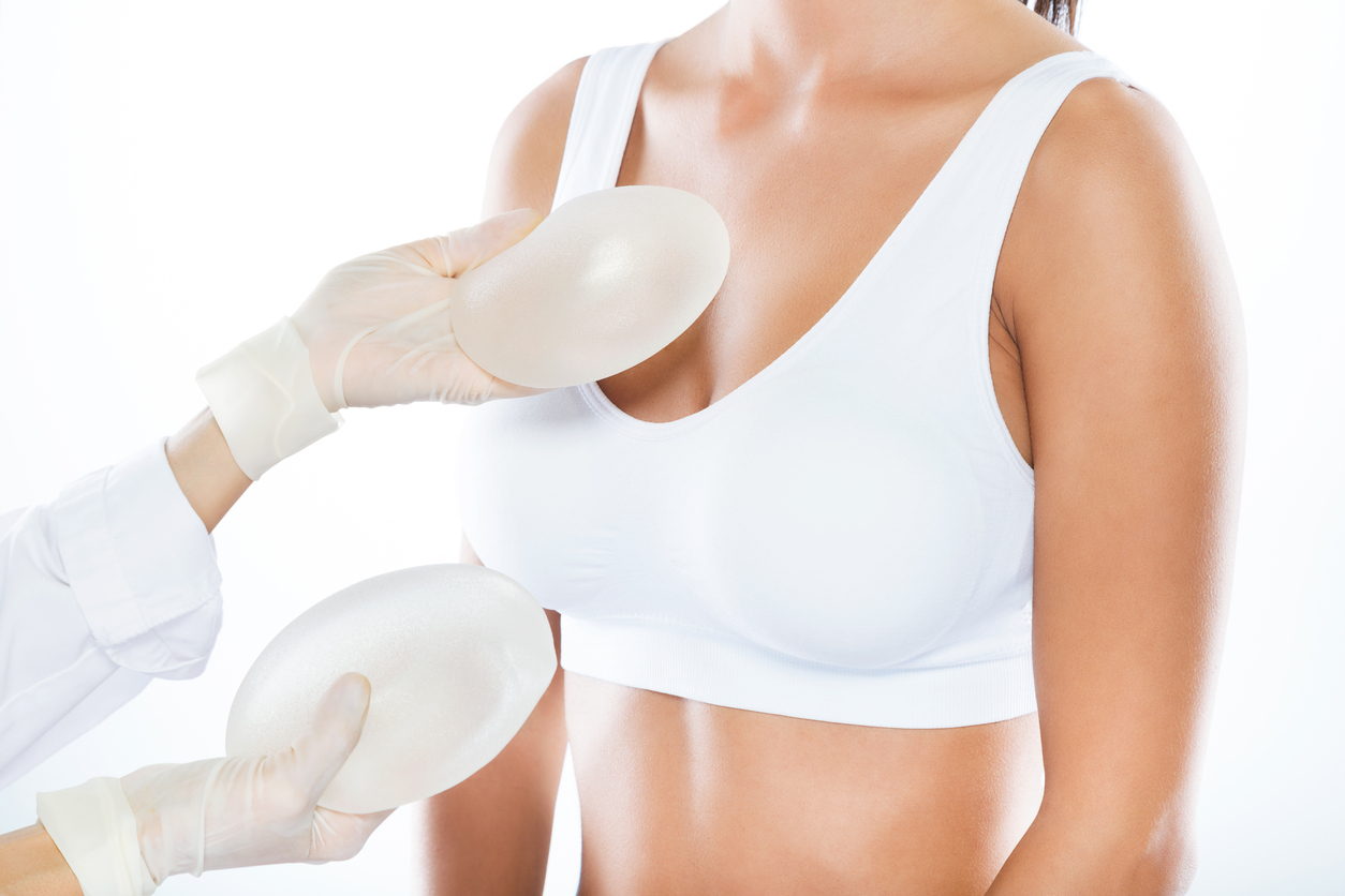 Female doctor choosing mammary prosthesis with her patient over white background.